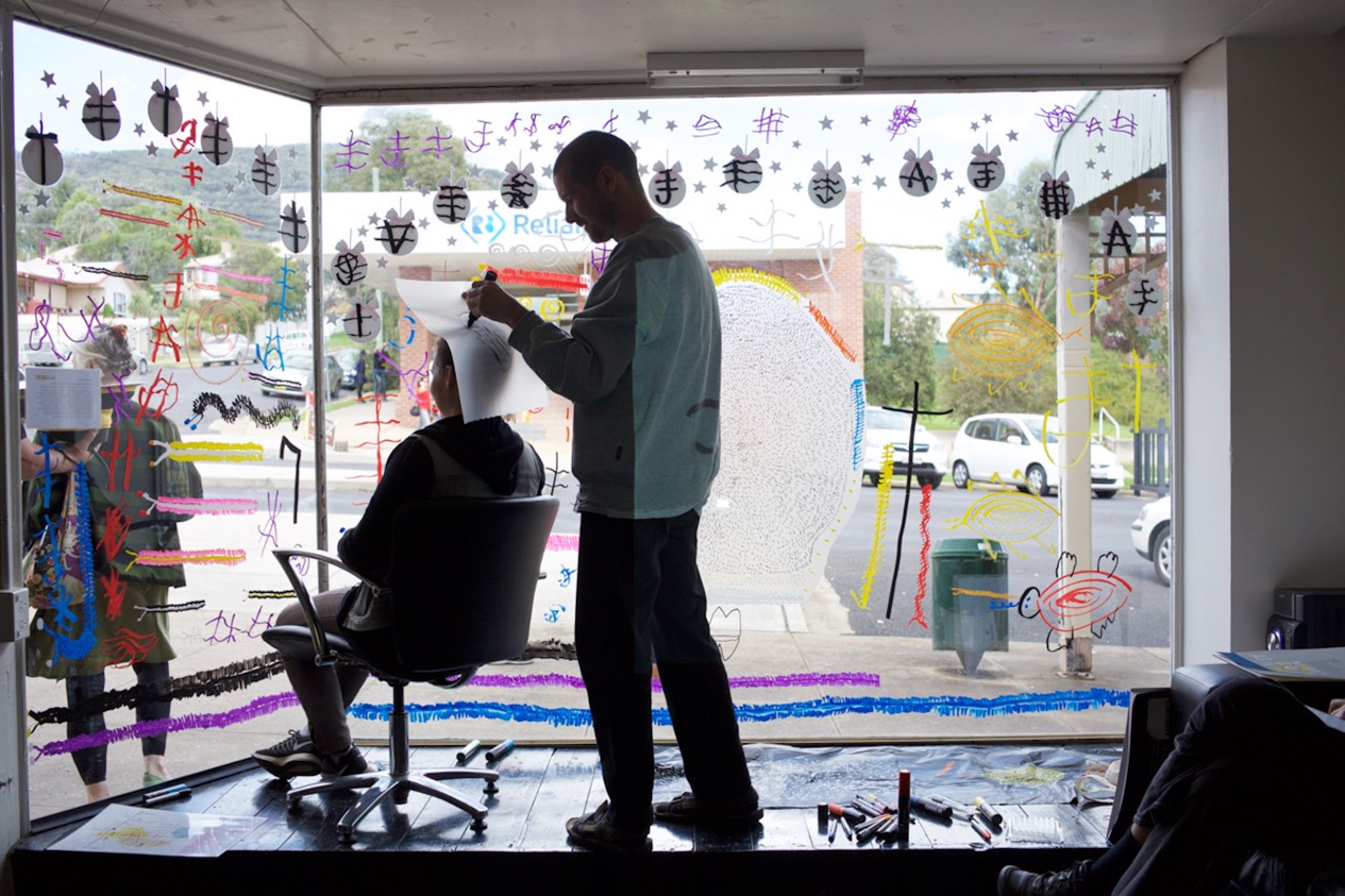 An artist stands in a display window reading/drawing the crown of a person's head.